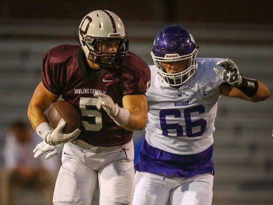 West Des Moines Dowling Catholic's Cole Deskin (5) breaks tackles against Waukee in the first half Friday, Sept. 16, 2016, in West Des Moines, Iowa.