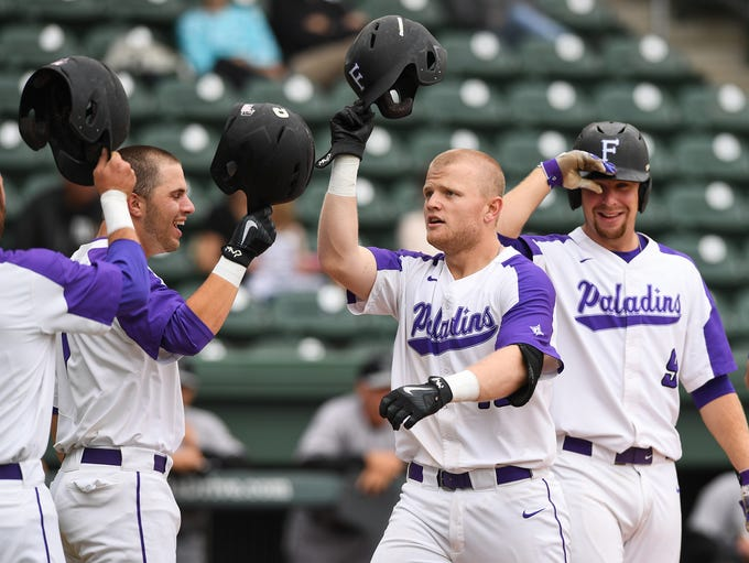 Furman's Cameron Whitehead (16) is congratulated by