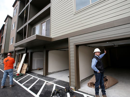Kelly Clark, president of Chinook Contractors, enters the garage of one of the units as he gives a tour of the Arendal on Viking apartment complex project in Poulsbo.