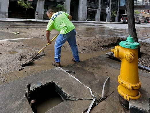 Des Moines Water Works employee Steve Graham, right, 50 of Des Moines, shoveled sand away Saturday from curbing so water could drain in front of the Equitable Building at 6th and Locust Street in Des Moines after an overnight fire.