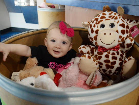 Mia Bonnema sits in a bin of stuffed animals donated by community members. The Bonnemas are holding a toy drive in honor of their first daughter Rylee who died in Feb. 2016.