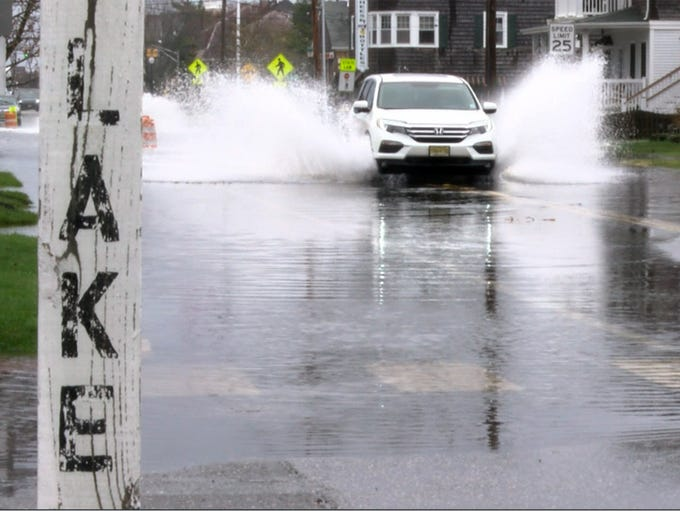A car splashes along Bridge Avenue, approaching West
