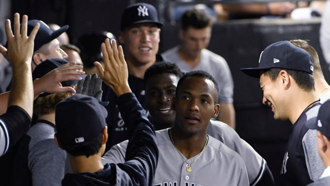 New York Yankees' Miguel Andujar, center, is greeted by teammates after hitting a home run against the Chicago White Sox during the seventh inning of a baseball game Tuesday, Aug. 7, 2018, in Chicago.