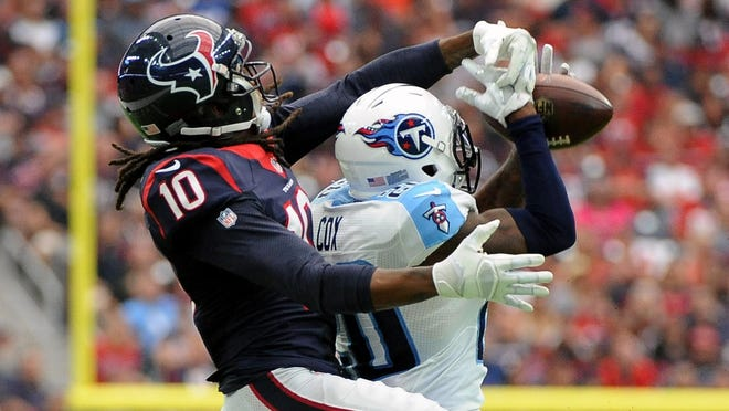 Titans cornerback Perrish Cox (20) intercepts a pass intended for Texans wide receiver DeAndre Hopkins (10) during the second half Sunday.