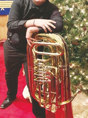 Doug Torres is pictured here with his favorite brass instrument, the tuba.
