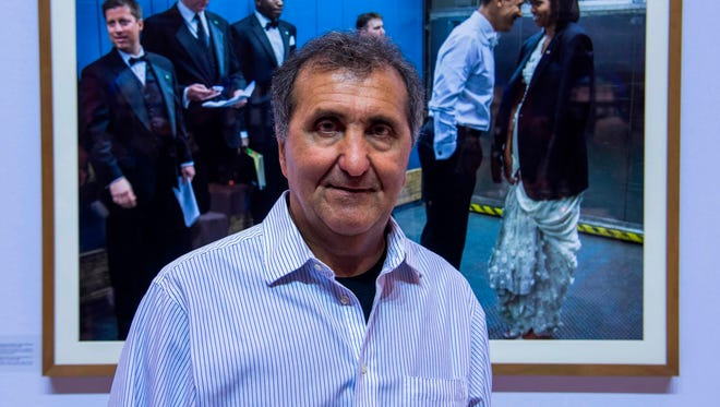 """Former White House photographer Pete Souza poses in front of one of his photographs during the launch of the German edition of his book: """"Obama: An Intimate Portrait"""", in Berlin on April 16, 2018."""