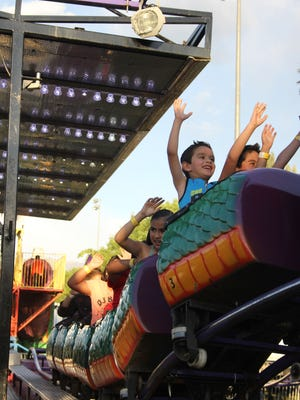 Children put their hands up on a roller coaster at a past Mesquite Days carnival at the Mesquite Recreation Center
