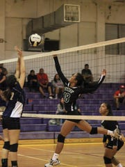 John F. Kennedy Islanders' Regine Tugade (18) attempts to tip the ball against the St. Paul Warriors during the 16th Annual Shieh High School Invitational Volleyball Tournament game at the George Washington High School Gym in Mangilao on Aug. 16.