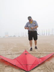 Due to the lack of the wind, fire and Ice performer Mark Ledvina, of Milwuakee, puts away his kite after attempting to perform with music with his teammates at the 10th annual Kites Over Lake Michigan at Neshotah Beach on Saturday, Sept. 5 in Two Rivers. The festival would run through the weekend.