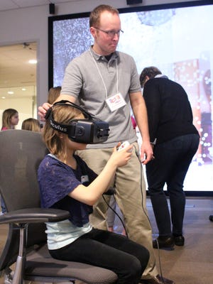 A young girl uses the Oculus Rift and a video game controller to navigate through a virtual rendering of a 3D scan of a real home.