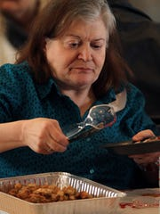 Emily Hart of Haskell, NJ, helps herself to stuffing as more than 100 people enjoyed a feast at NewBridge Services 22nd annual Thanksgiving celebration at the First Reformed Church of Pompton Plains. November 25, 2015, Pompton Plains, NJ.