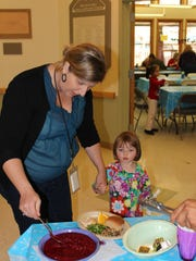 Reporter Beth Walton and Harper Marchal, 3, make a plate at Verner Center for Early Learning's Family Feast. The educational day care engages parents in school happenings.