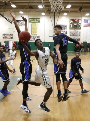 Lincoln's Dwight Wilson tries to lay the ball up between Godby defenders Jeremy Myers, right, and Tre Clemons during their game at Lincoln High School on Thursday. The Cougars won 72-61 on the road.