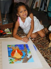 Avery McCaskill poses with her painting of an owl.