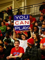 A student displays a sign during the Stony Brook men's