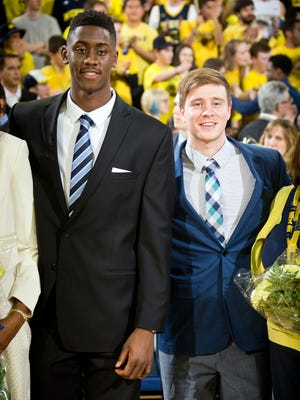 """Michigan guard Caris LeVert, left, and guard Spike Albrecht, right, are honored during """"Senior Night"""" before the game against Iowa at Crisler Center."""