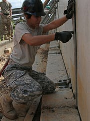 Spc. Elizabeth Fernandez, a Louisiana National Guardsman from the 1022nd Engineer Co. originally from Salem, Oregon, secures emergency barriers on the banks of the Ouachita River in Monroe, La., March 13, 2016.  The 1022nd has been constructing the concrete levees to combat rising river levels caused by the excessive rainfall over the past few days.