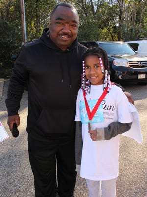 Brantwood Children's Home Executive Director Gerald Jones congratulates Dynastee Hunter, 9, for finishing first in her age group at the facility's Love Run. Dynastee is the daughter of a volunteer who helped with the race. Alvin Benn/Special to the Advertiser.