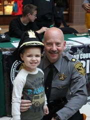 Caleb Aviles, 3, poses with Vince Solazzo of the Cumberland County Sheriff's Office after being made an honorary deputy.