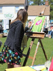 Heather Anne Sines of The Painted Trove paints during the Art Walk. Her art work can be found on Facebook.