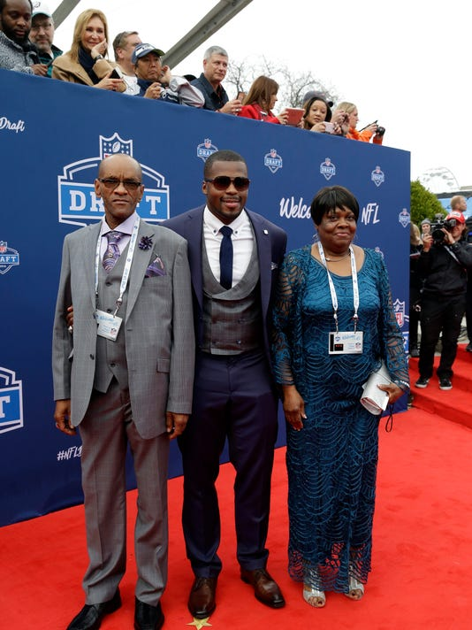 Alabama's Reggie Ragland, center, poses for photos upon arriving for the first round of the 2016 NFL football draft at the Auditorium Theater of Roosevelt University, Thursday, April 28, 2016, in Chicago. (AP Photo/Nam Y. Huh)