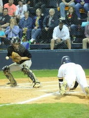 Northeast's Cameron Norris slides into home plate for