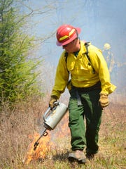 David Wilcox of the Vermont Department of Forests, Parks & Recreation, uses a special torch to initiate the edge of the burn.  The team works hard to make sure that the edges of the fire burn first to use up all available dry wood and grass in order to control the area of the burn.