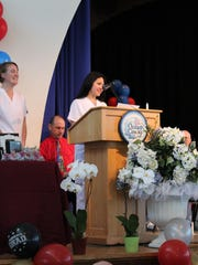 Andrea Mendoza, student government representative, gives the opening remarks during the annual pinning ceremony as class president Meghan Dawson (left) listens.