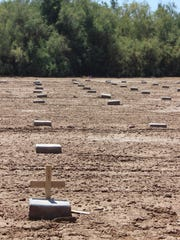 Crosses and stones mark the graves of unidentified and unclaimed bodies in a Potter's Field behind Terrace Park Cemetery in Holtville.