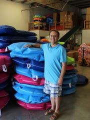 Jayson Putnam stands with a stack of GoodLife Designs pool floats. Jayson is one of the co-owners who purchased the company in 2004.