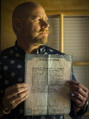 Casey Gradischnig, a trans man, poses with his birth certificate Thursday, June 9, 2016, at his home in Des Moines.