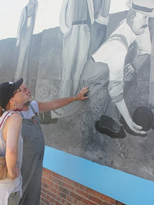 Doug DeBrower, right, and Samantha Anderson, HLV High School art teacher, look over a part of a mural during a dedication ceremony Saturday, June 25, in Victor, as part of Victor Fun Day.