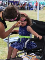 Emily Alprin, 3, gets her face painted at the Red, White and Blueberry Festival.