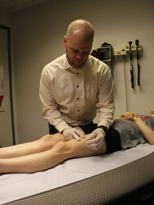 Physical therapist Matt Briggs treats a patient with dry needling at The Ohio State University Wexner Medical Center.
