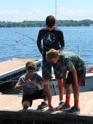 Tomas Martinez (center), 16, a counselor-in-training from Venezuela teaches campers how to fish on Monday at YMCA Camp Abnaki in North Hero.