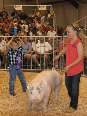 William Kintzler shows off his sister, Savanna Kintzler's hardware as she leads her grand champion hog in the ring during the 2016 Fond du Lac County 57th annual Meat Animal Sale held in the Cow Palace at the Fond du Lac County Fair July 21.