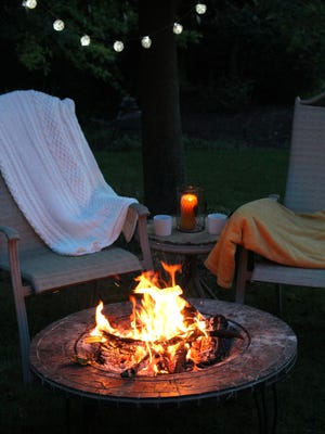 String lights, candles and a fire pit create a warm atmosphere at an outdoor fall party. Cozy up to the fire with lawn chairs and blankets.