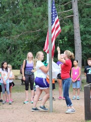 Youth stand respectfully as older members raise the American flag during a 4-H activity.
