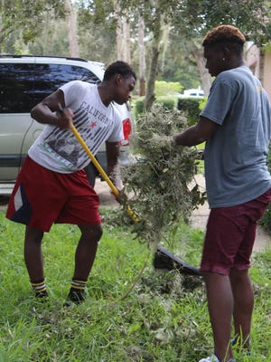 Moses Walters and Gibran Williams clean up a yard in Sherwood Estates.