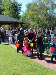 Children begin the costume parade in front of the gazebo in Saw Mill Park.