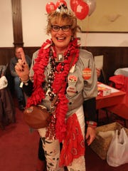 """Linda """"Flossie"""" Mills, a 1974 OSU grad and Mansfield resident, poses at the Beat Michigan Buckeye Bash on Monday, Nov. 21, 2016. Lokai predicted the Buckeyes will beat the Wolverines by two touchdowns in Saturday's game."""