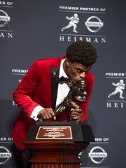 Lamar Jackson kisses the Heisman Trophy.