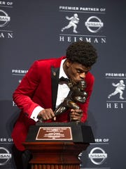 Lamar jackson kisses the Heisman Trophy. Dec. `10, 2016