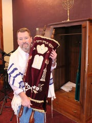 Rabbi William Hallbrook of Mansfield's Sar Shalom Messianic Congregation holds the Torah scrolls on Monday. The congregation's scrolls are handwritten and between 150 and 200 years old. The congregation's menorah is visible on top of the ark, where the scrolls are kept.