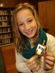 Gabby Person holds a dreidel that is a popular learning