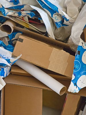 Trash bins spill over with torn wrapping paper, cardboard rolls, envelopes, boxes, and more