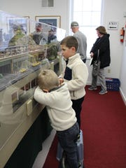 Andrew Datz, 2 (front) and his older brother Evan, 5, peer through the glass to get a better look at the trains.