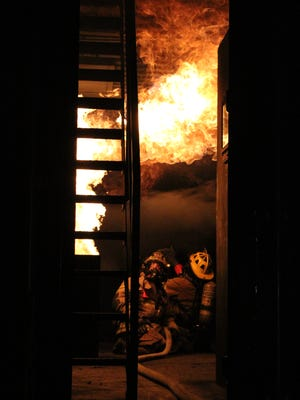 Firefighters watch as flames roll across the ceiling of the newly rededicated Holiday Village Fire Department's burn trailer. The trailer is used for training exercises.