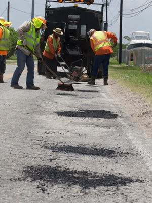 Rachel Denny Clow/Caller-TimesCity employees fill potholes on Laguna Shores Road on Tuesday, July 7, 2015.