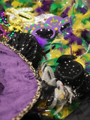 A pile of Mardi Gras accessories sat on a table outside of a photo booth at the Meals on Wheels of Anderson's Mardi Gras party.